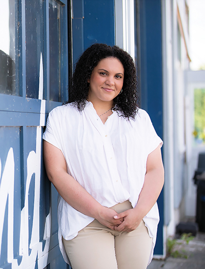 Black woman with curly hair wearing a white blouse and khaki pants stands in front of a blue wall.