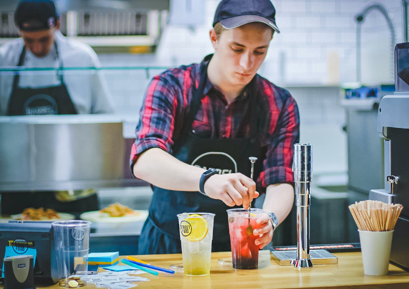 A young man in a plaid shirt stirs a drink while standing behind the counter of a restaurant