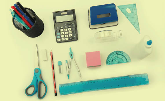 High school school supplies like a calculator, protractor, ruler and more on a pale yellow background