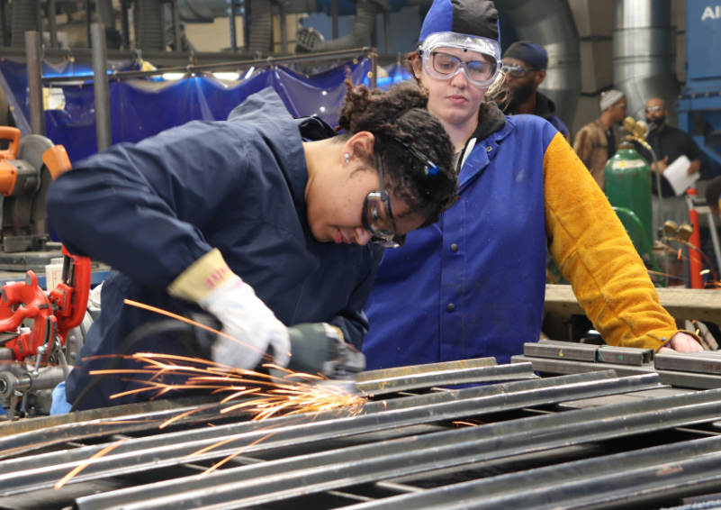 A picture of one woman watching another working in a machine shop as sparks fly.