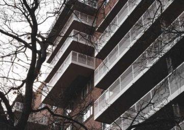 Exterior shot of a brick apartment building with several decks.
