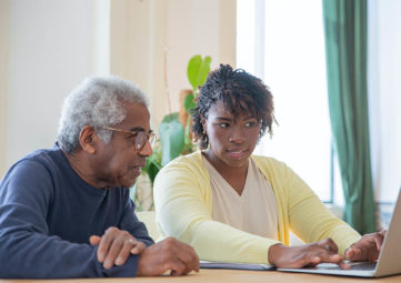An older man and young woman look at a laptop on a table.