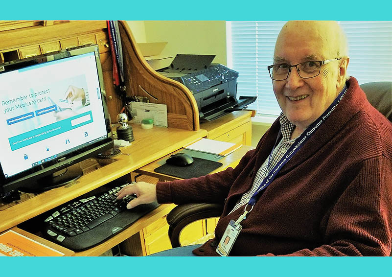 An elderly white man with glasses and a cardigan sits at a computer with Medicare information showing on the screen