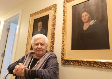 Elderly white woman seated in front of two large portraits of her parents